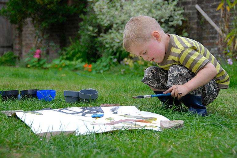 Young Gifted and Talented Boy Painting Outdoors
